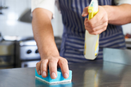 Close Up Of Worker In Restaurant Kitchen Cleaning Down After Service