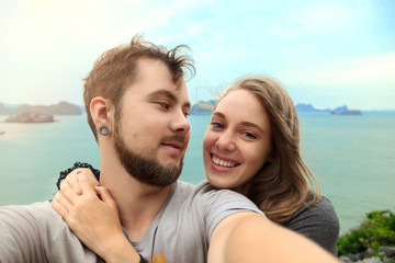 Happy young man and woman taking self portrait with sea scenery in background.