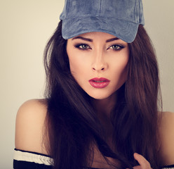 Beautiful sexy young make-up model posing in blue baseball cap with long hair style. Toned closeup portrait