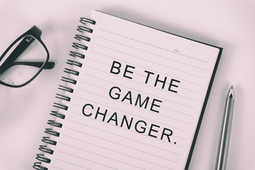 Inspirational quote - be the game changer: written on a note pad with eyeglasses and pen.