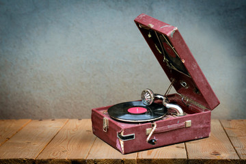 Old vintage gramophone player with a vinyl record in it in a dark red case on wooden table against old grunge wall background