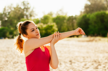 Attractive woman stretching arm after run on beach.