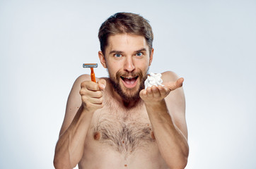 A young guy with a beard on a light background holds a shaving foam and a razor