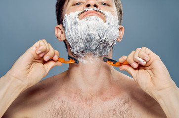 Young guy with a beard on a gray background shaves
