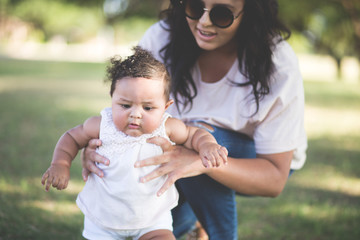Young mother enjoys her infant daughter at the park