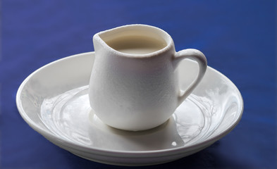 White ceramic creamer on a saucer with cold cream on a blue background.