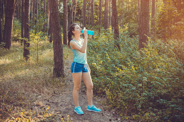 Runner drinking water in the forest
