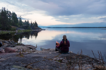 A woman sits by the fire on the stone shore of a large lake. Evening. In the background, you can see a promontory with trees.