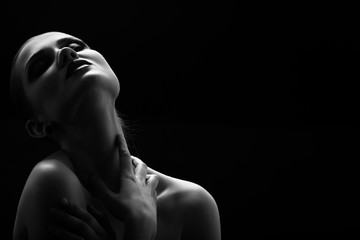 Black and white shot of woman posing sensually holding head up on black background, monochrome