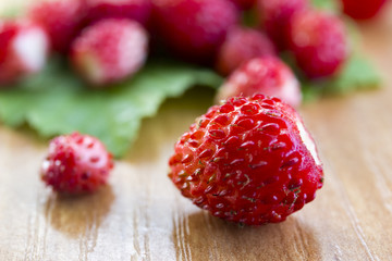 fresh wild strawberries on the leaf and table, healthy nutrition, close-up macro
