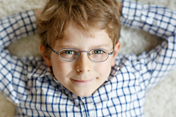 Close-up portrait of little blond kid boy with brown eyeglasses