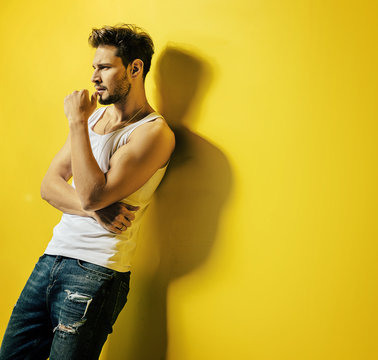 Handsome man leaning on the bright, yellow wall