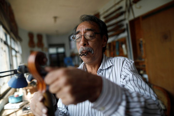 Arturo Moreno, 62,  a luthier and archetier, uses pitch pipe & tone generator for tune a violin at his workshop in Mexico City