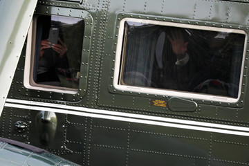 Trump waves and the first lady takes pictures as they depart aboard the Marine One helicopter for travel to France from the South Lawn of the White House in Washington
