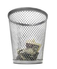 Isolated dollar bills inside a trash bin.