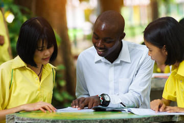 American teacher teaching asian student about foreign languages.