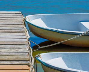2 small rowboats tied to a weathered wooden dock on a Massachusetts lake