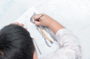school boy drawing picture with color pencil,
