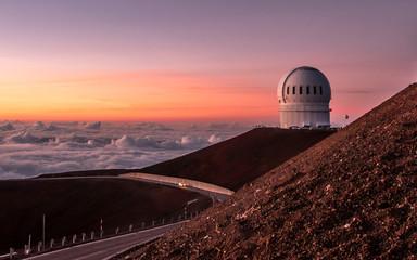 Observatory domes at the peak of Mauna Kea volcano under sunset