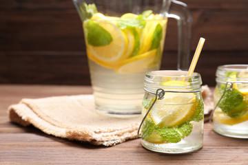 Jars and jug of fresh lemonade on wooden background