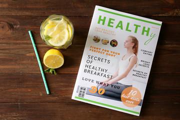 Fototapete - Glass of fresh lemonade and magazine on wooden background