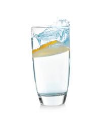 Glass of lemonade with splashing water on white background