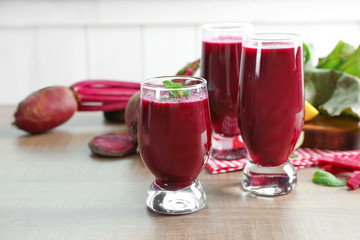Glasses with fresh beet smoothies on wooden table