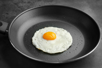 Photo sur Toile Ouf Homemade over easy fried egg in pan on dark background