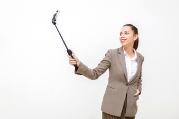 happy young asian business woman in suit beautiful smiling taking selfie with mobile smartphone on selfie stick isolated on white background, social media network technology and lifestyle concept