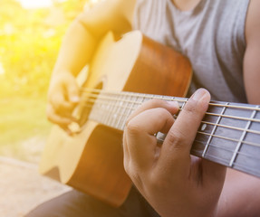 Man hands playing acoustic guitar, close up