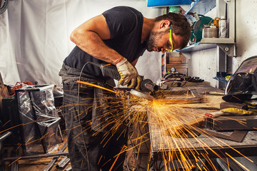 man weld in a processes a metal  with a  angle grinder