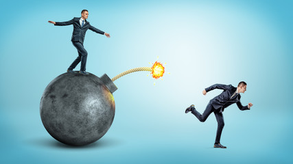 A businessman standing on a black round bomb with a lit fuse beside a man running away from it.