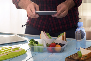Man photographing lunch box with healthy food