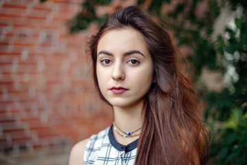 Closeup portrait of beautiful pensive young middle eastern Caucasian jewish woman with long dark hair, black brown eyes, looking in camera. Girl in white plaid shirt against brick wall. Natural beauty