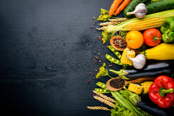 A large selection of raw fresh vegetables and spices. On a black wooden background. Top view. Free space for your text.