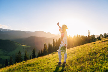 Woman feel freedom and enjoying the nature in the mountains green fern leaves in hands on sunset