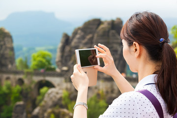Taking Pictures of Tourist Attraction / Young asian female tourist take photographs with mobile phone of famous Bastei rock formation and bridge in Saxon Switzerland National Park, Germany