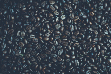 Dark roasted coffee beans background and texture