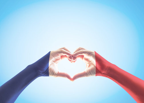 France national flag pattern on people's hands in heart shape on blue sky background (isolated with clipping path)