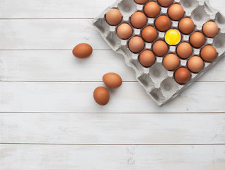 Top view of chicken eggs in a cardboard box on a white wooden table with copy space.