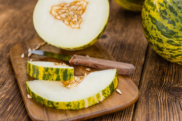 Portion of Fresh Futuro Melon on wooden background (selective focus)