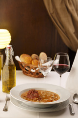 Bean soup arranged in a plate, Wineglass in background, Traditional dish in elegant setting, Selective focus with soft light