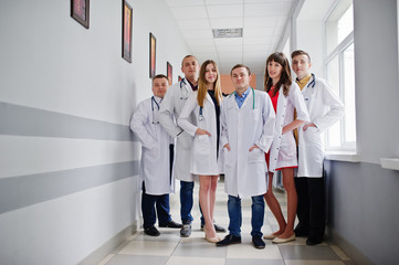 Group of young doctors in white coats posing in the hospital.