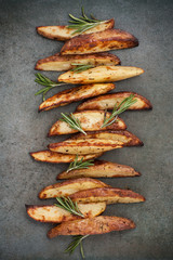 Slices of baked potatoes with rosemary on a textured stone table..