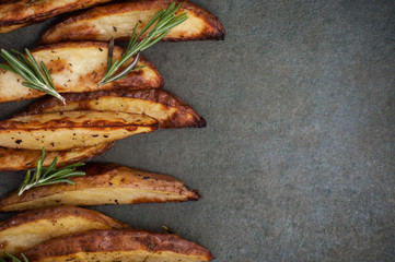 Slices of baked potato with rosemary close-up on a textured stone table..