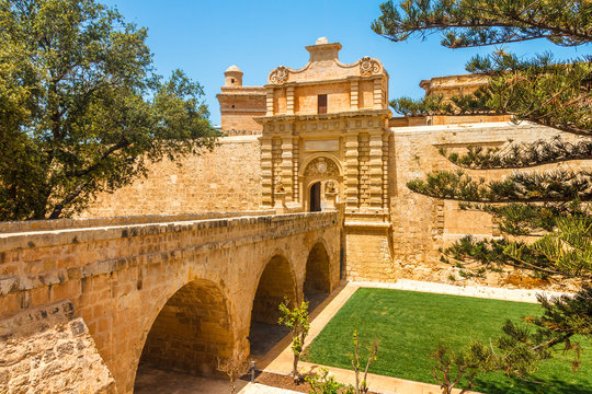 Entrance bridge and gate to Mdina, a fortified medieval city in the Northern Region of Malta.