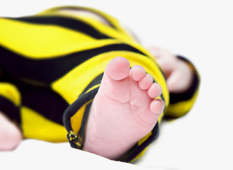 A young babys foot, shot  close up in a white studio, with the rest of the body out of focus with a shallow depth of field.