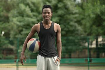 Portrait of african american man on basketball court keep ball