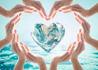 World heart day and environmental protection concept with love earth in community volunteer's hands. Element of this image furnished by NASA