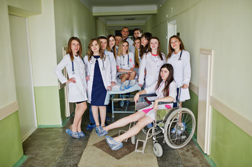 Crazy young doctors having fun by posing on a wheelchair in the hallway of hospital.